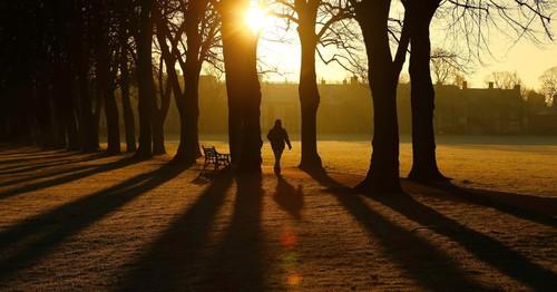 30dez2014---homem-caminha-ao-nascer-do-sol-atraves