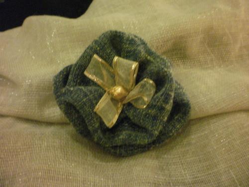 Pregadeira em tecido em tons de azul com fita e pedra douradas.
